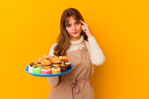 Femme jeune chef pâtissier isolée sur fond jaune pointant le temple avec le doigt, pensant, concentré sur une tâche.