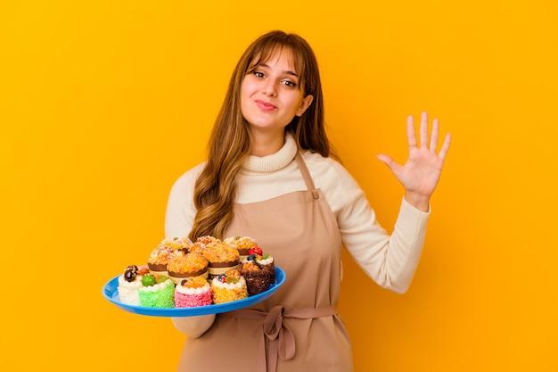 Femme jeune chef pâtissier isolée sur fond jaune souriant joyeux montrant le numéro cinq avec les doigts.