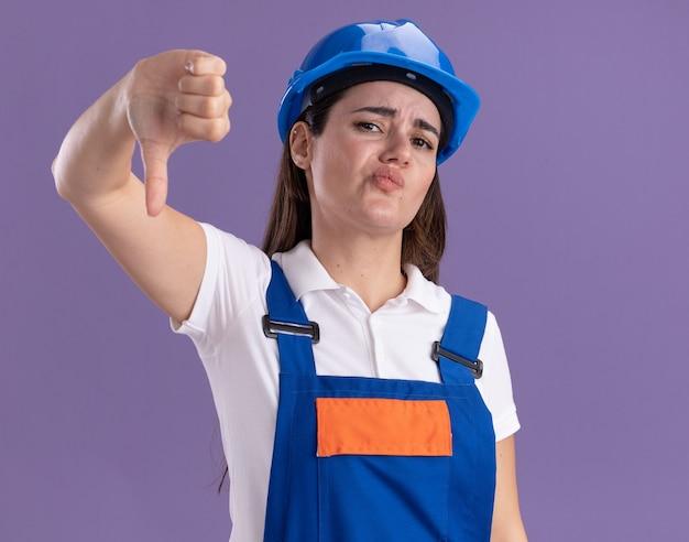 Femme jeune constructeur insatisfait en uniforme montrant le pouce vers le bas isolé sur mur violet