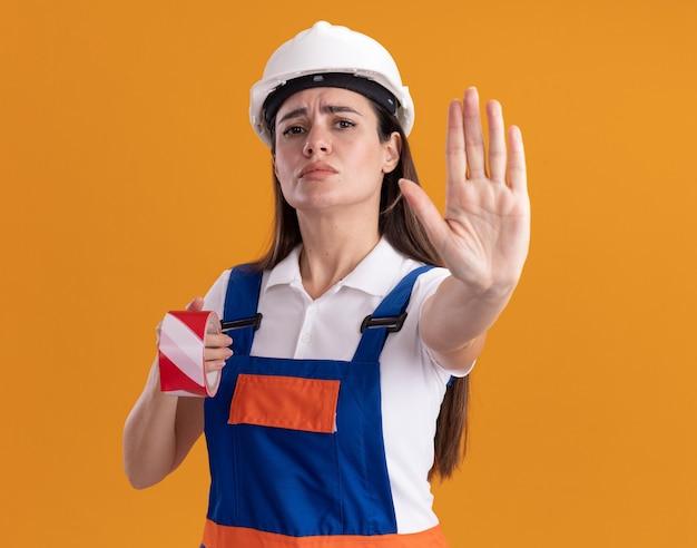Femme jeune constructeur strict en uniforme tenant du ruban adhésif et montrant le geste d'arrêt isolé sur un mur orange