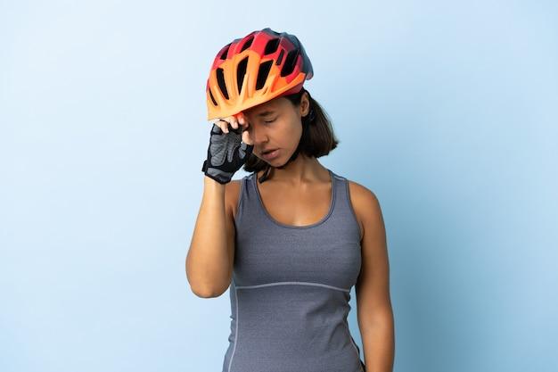 Femme jeune cycliste isolée sur fond bleu avec une expression fatiguée et malade