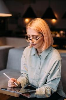 Femme jeune designer créatif dans des verres tenant le stylet