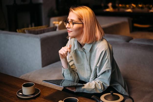 Femme jeune designer créatif dans des verres tenant un stylet