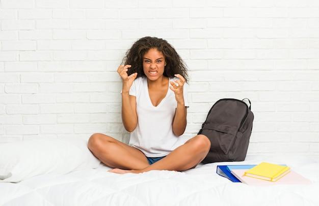 Femme jeune étudiante afro-américaine sur le lit contrarié crier avec les mains tendues.