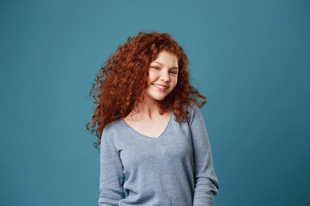 Femme jeune étudiante gaie avec des cheveux roux ondulés et des taches de rousseur souriant brillamment montrant ses dents, posant pour l'album photo de fin d'études.
