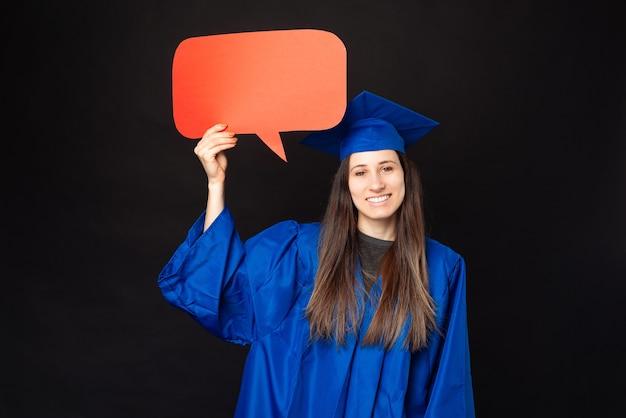 Femme jeune étudiante joyeuse portant baccalauréat bleu et bonnet de graduation et tenant une bulle de dialogue vide