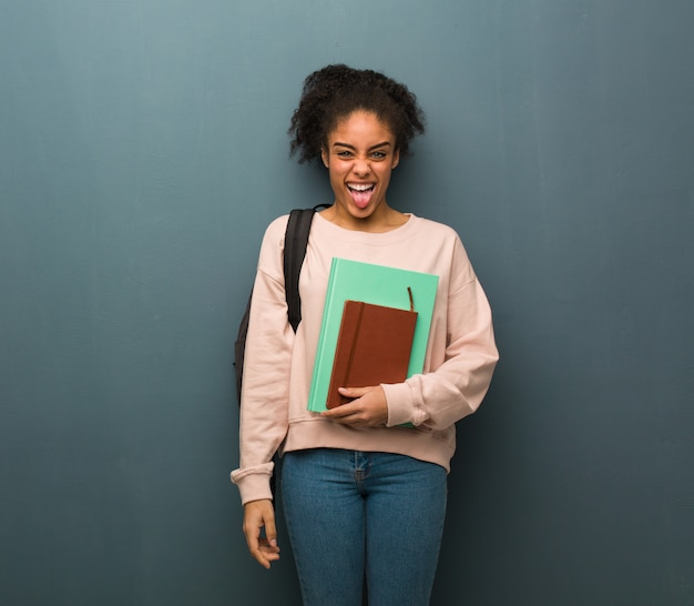 Femme jeune étudiante noire drôle et sympathique montrant la langue. elle tient des livres.