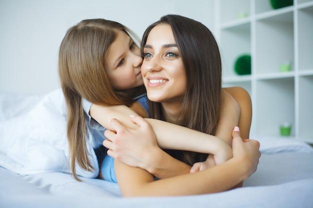 Femme et jeune fille au lit souriant
