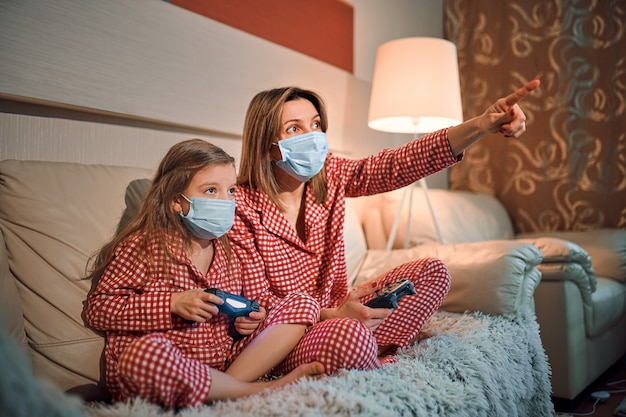 Femme et jeune fille portant un pyjama et des masques de protection médicale assis sur un canapé dans le salon avec des contrôleurs de jeux vidéo à la maison, isolement automatique en quarantaine, covid-19.