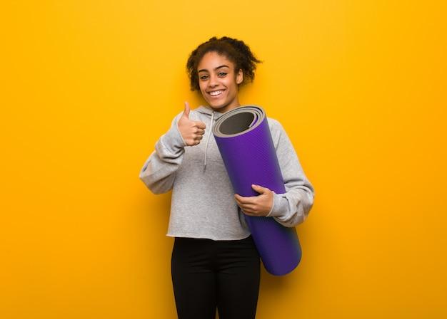 Femme jeune fitness noir souriant et levant le pouce. tenant un tapis.