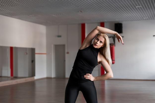 Femme jeune formateur professionnel en vêtements de sport noirs engagés dans un studio de remise en forme