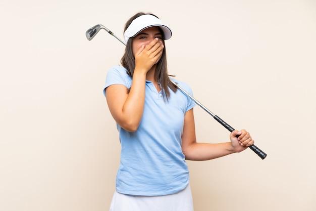 Femme jeune golfeur sur mur isolé avec une expression faciale surprise