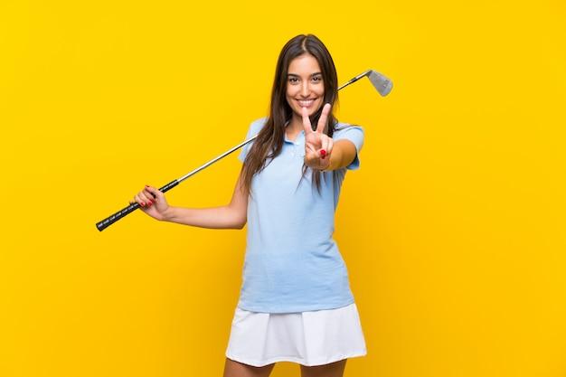 Femme jeune golfeur sur mur jaune isolé, souriant et montrant le signe de la victoire