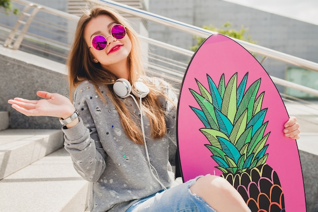 Femme jeune hipster dans la rue avec planche d'équilibre portant pull et jeans
