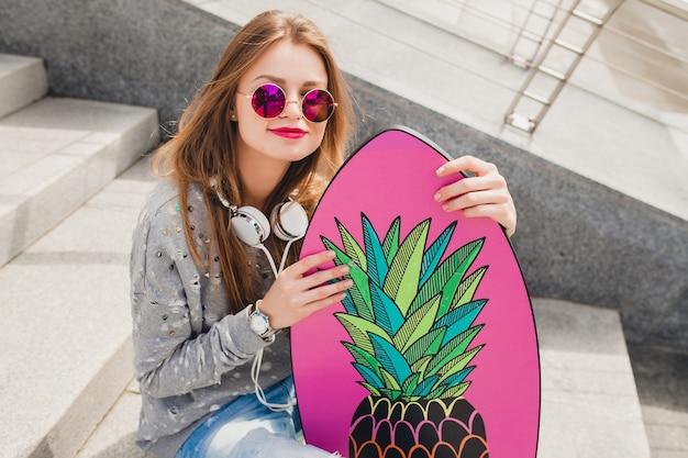 Femme jeune hipster en lunettes de soleil roses dans la rue avec planche d'équilibre portant pull et jeans