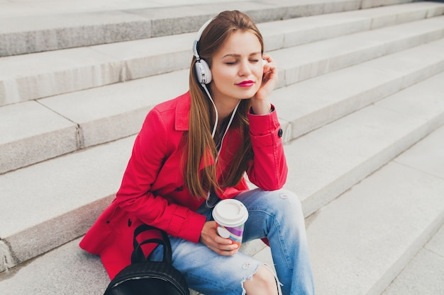 Femme jeune hipster en manteau rose, jeans assis dans la rue avec sac à dos et café en écoutant de la musique au casque