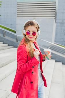 Femme jeune hipster en manteau rose, jeans dans la rue avec du café en écoutant de la musique au casque