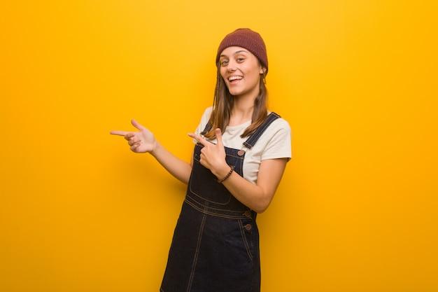 Femme jeune hipster pointant sur le côté avec le doigt