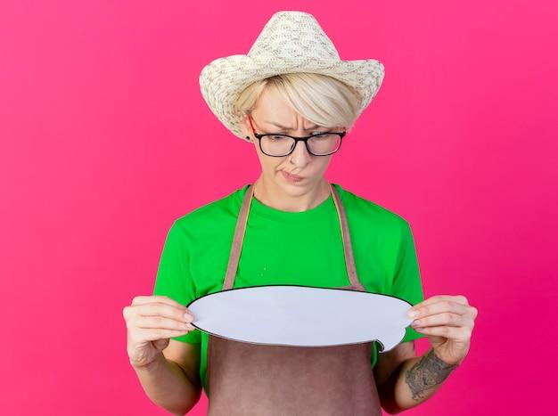 Femme jeune jardinier aux cheveux courts en tablier et chapeau tenant une bulle de dialogue vierge