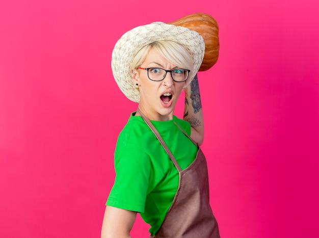 Femme jeune jardinier aux cheveux courts en tablier et chapeau tenant la citrouille