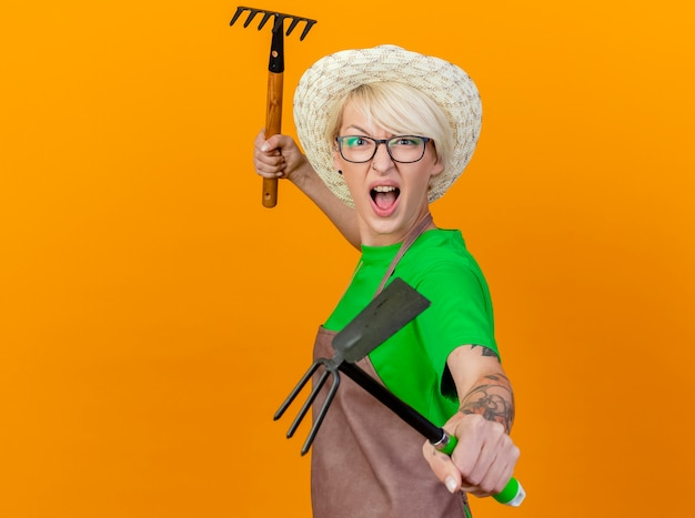 Femme jeune jardinier aux cheveux courts en tablier et chapeau tenant mattock et mini râteau regardant la caméra avec visage en colère criant debout sur fond orange