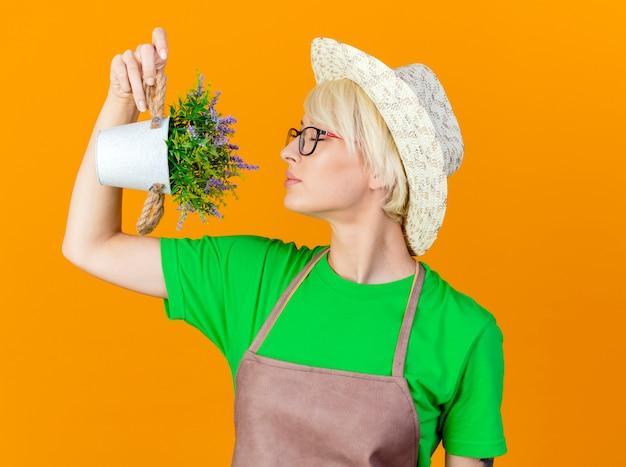 Femme jeune jardinier aux cheveux courts en tablier et chapeau tenant une plante en pot