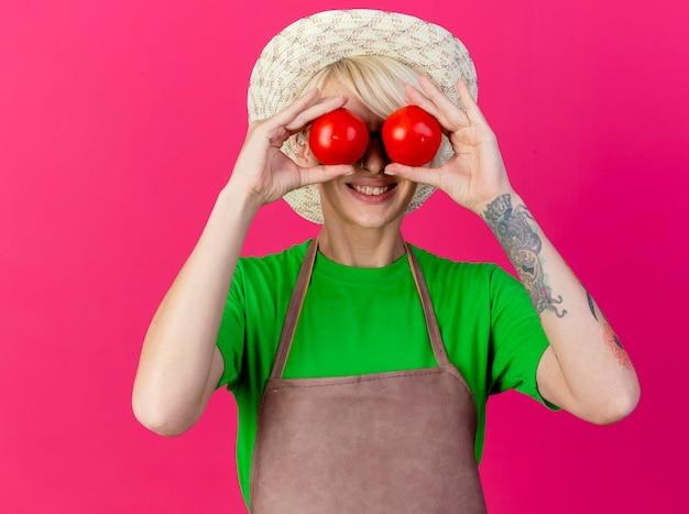 Femme jeune jardinier aux cheveux courts en tablier et chapeau tenant des tomates fraîches