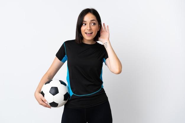 Femme jeune joueur de football isolé sur blanc en écoutant quelque chose en mettant la main sur l'oreille