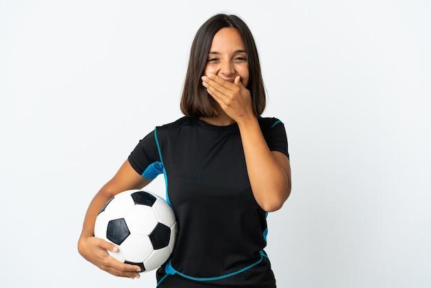 Femme jeune joueur de football isolé sur blanc heureux et souriant couvrant la bouche avec les mains