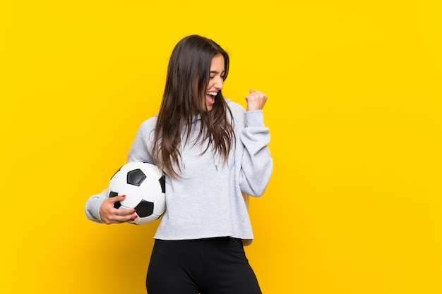 Femme jeune joueur de football sur mur jaune isolé célébrant une victoire