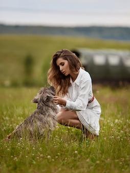 Femme jeune mannequin en robe courte blanche posant avec un chien mignon sur la prairie