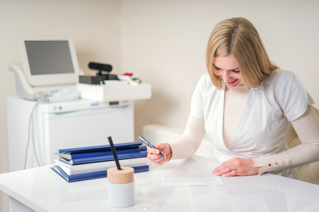 Femme jeune médecin écrit assis à son bureau avec du matériel médical. concept de soins de santé et médical