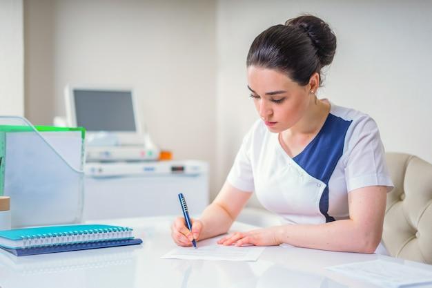 Femme jeune médecin écrit quelque chose assis à son bureau. concept de soins de santé et médical