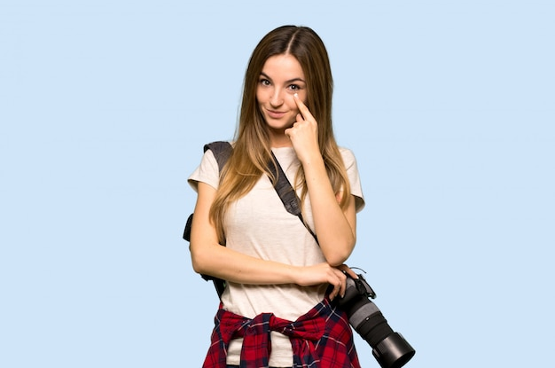 Femme jeune photographe à la recherche sur le mur bleu isolé