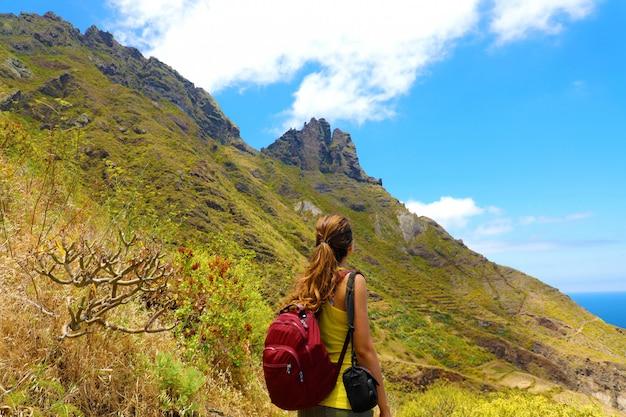 Femme jeune randonneur regardant le sommet de la montagne