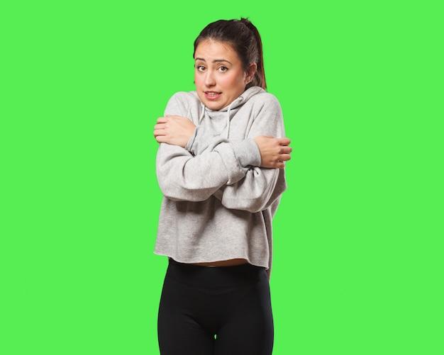 Femme jeune de remise en forme devient froide en raison de la température