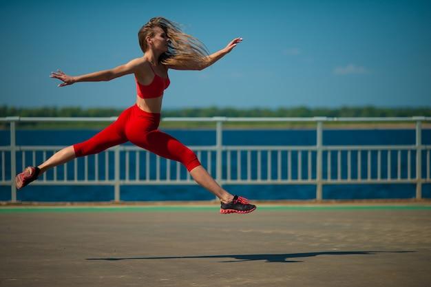 Femme jeune de remise en forme qui court sur la côte. le concept d'un mode de vie sain