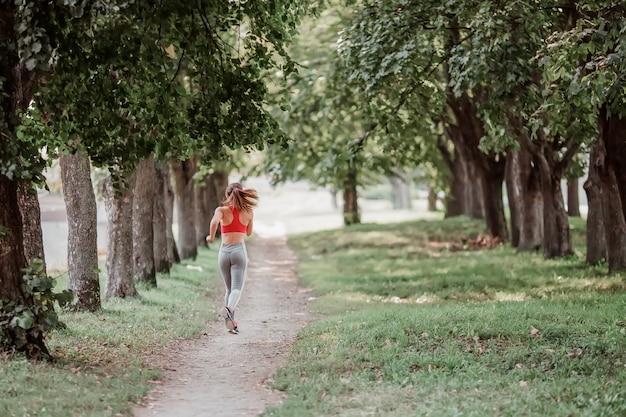 Femme jeune de remise en forme qui court dans le parc.