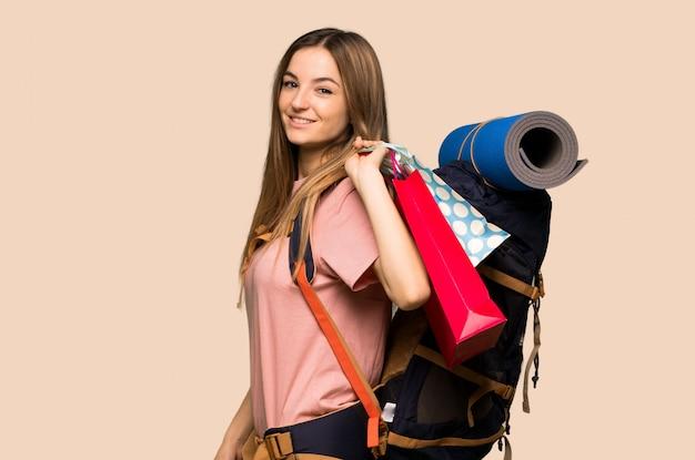 Femme jeune routard tenant beaucoup de sacs à provisions sur fond jaune isolé