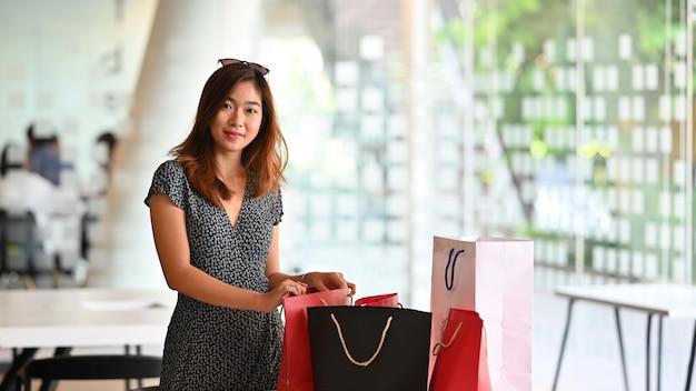 Femme jeune shopper en regardant la caméra avec le sac sur la table, concept shopaholic.