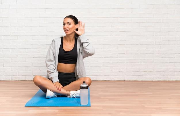 Femme jeune sport assis sur le sol avec tapis écoute quelque chose