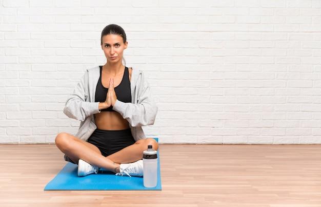Femme jeune sport assis sur le sol avec tapis plaidant