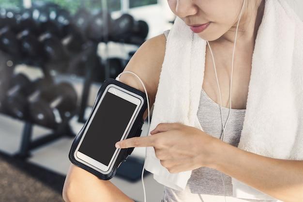 Femme jeune sport dans la salle de gym à l'aide de smartphone, fitness, formation concept lifestyle