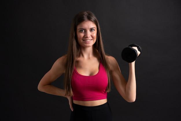 Femme jeune sport faisant de l'haltérophilie sur fond noir isolé