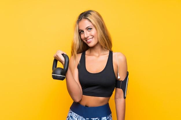 Femme jeune sport faisant de l'haltérophilie avec kettlebell sur jaune isolé