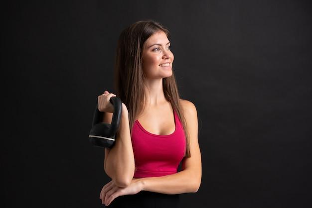 Femme jeune sport faisant de l'haltérophilie sur un mur noir isolé