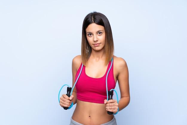 Femme jeune sport sur mur bleu isolé avec corde à sauter