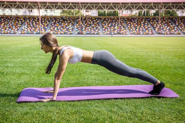 Femme jeune et sportive faisant exercice de planche sur tapis sur l'herbe verte à l'extérieur
