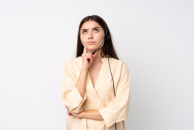 Femme jeune télévendeur sur blanc isolé, pensant une idée