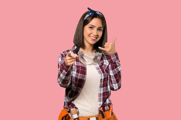 Femme jeune travailleur faisant un geste de téléphone et pointant le devant sur un mur rose isolé